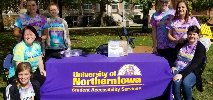 SAS staff sitting or standing around a table with a purple UNI SAS tablecloth during the Fall 2019 T-Dye Event.